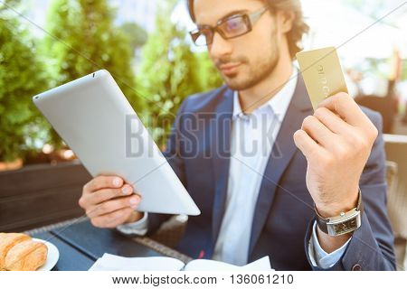 Busy young businessman is paying for service in restaurant. He is holding a credit card. Man is sitting and using a tablet with interest