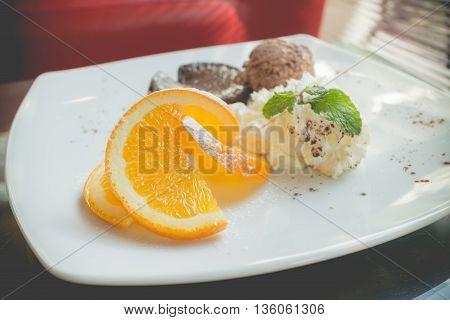 chocolate lava cake set with ice cream and sliced orange on white plate