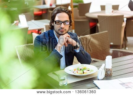 Pensive young man is having breakfast in restaurant. He is sitting at table and looking forward with seriousness