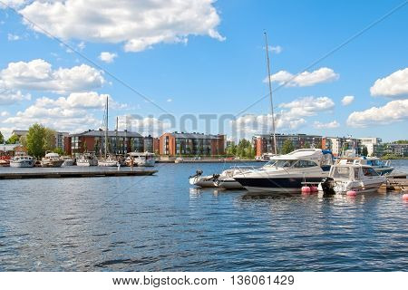 LAPPEENRANTA, FINLAND - JUNE 15, 2016: Pier with yachts and boats on Saima Lake. On the background are residential buildings on Rapasaari Island