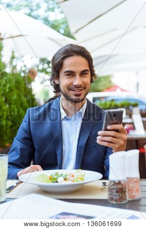 Successful young businessman is resting in restaurant. He is sitting at table and holding phone. Man is looking at camera and smiling
