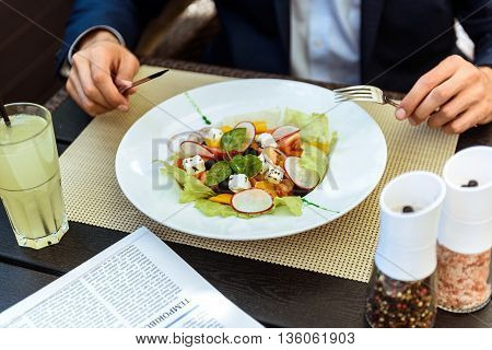 Close up of hands of man eating salad in restaurant