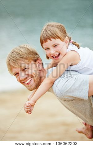 Happy father carrying smiling daughter piggyback in summer on a beach
