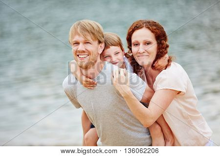 Happy family with daughter on summer vacation at sea