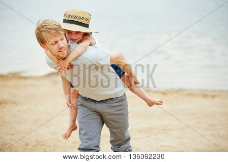 Man carrying girl piggyback on his back on a beach in summer