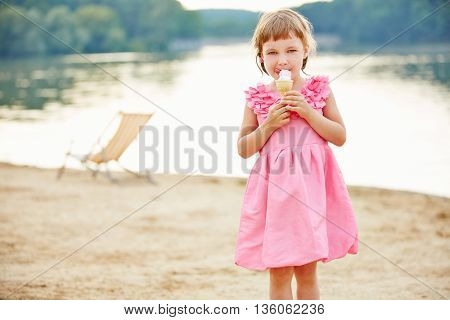 Girl eating ice cream cone in summer on beach of a lake