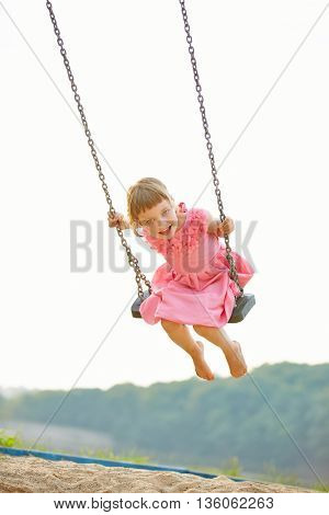 Happy child sitting and swinging on swing in summer