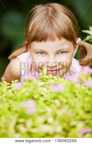 Smiling girl playing hide and seek in garden and hiding behind a bush