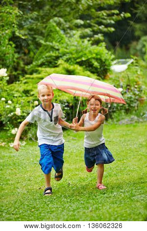 Two happy children running under an umbrella in the rain in a garden