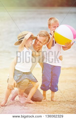 Happy father playing with son and daughter on beach in summer