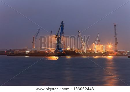 Industrial quay of Hamburg. Giant machines highlighted at night