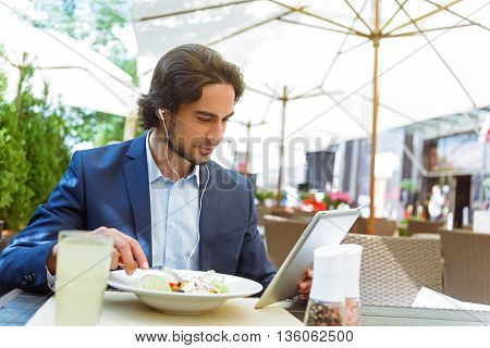 Successful young businessman is eating salad in restaurant with enjoyment. He is watching something on tablet. Man is sitting at table and wearing headphones