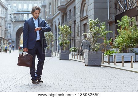 Busy young man is waiting for client. He is standing outdoors and looking at watch with seriousness. Worker is carrying a briefcase