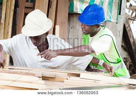 The teacher teaches the student how to measure the boards to have well made furniture.