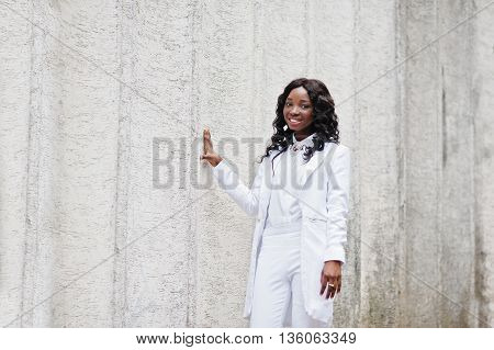 Young African American Girl, Dressed In White, Background White Stone Wall