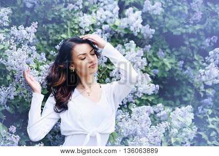 Beautiful woman in a spring garden with blooming lilacs