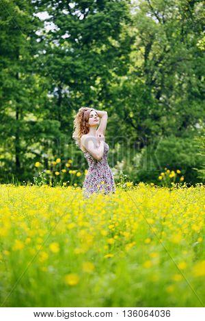 Woman walks through a field of buttercups