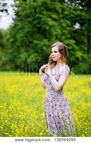 Woman walks through a field of buttercups, Portrait of a woman with curly hair