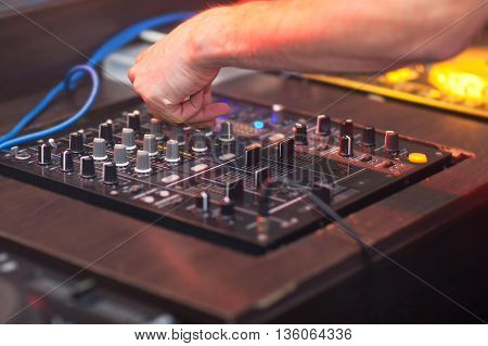DJ mixing music on console at the night club.