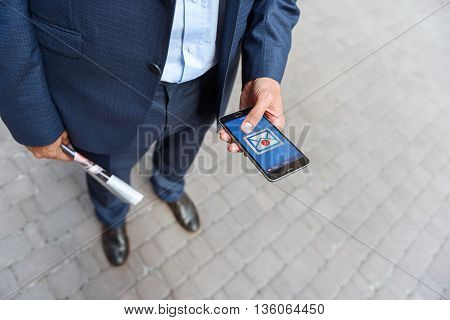 Close up of businessman opening message on mobile phone. He is standing with newspaper in his hand