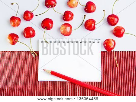 Blank spiral notepad, pencil and ripe cherries on  red corrugate cardboard paper and white tablecloth, space for text or message