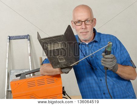 portrait of mature man with a welding station