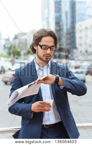 Confident young man is looking at his watch with anticipation. He is standing outdoors. Worker is hold a cup of coffee and newspaper