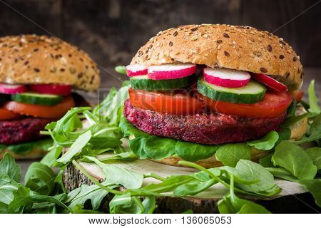 Veggie beet burgers with lamb's lettuce, tomato, radish and cucumber on rustic wooden background
