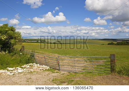 a pair of broken metal gates in scenic farmland in the yorkshire wolds under a blue cloudy sky