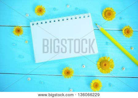 Blank spiral notepad, pencil, pearl beads and yellow chamomiles blossoms on painted blue wooden background, space for text or message