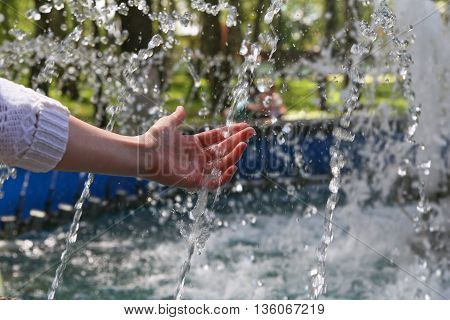 Hand touches clean and fresh water from the fountain.