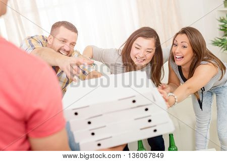 Four cheerful friends enjoying pizza together at home party. Selective focus.