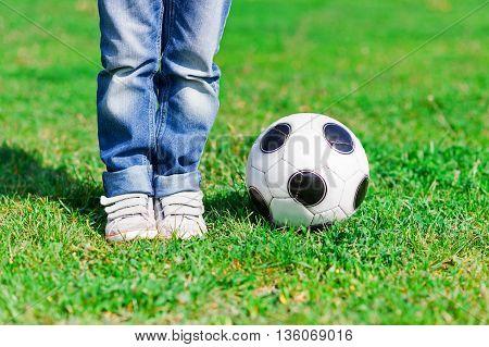Close up of feet of boy standing on grass near a ball