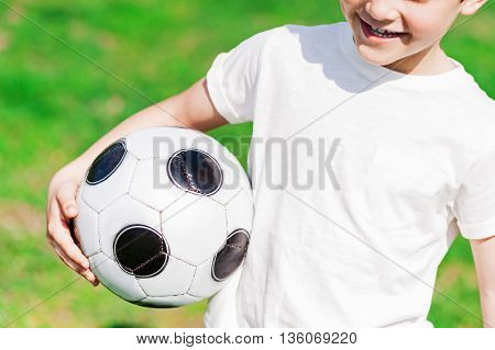 I like football. Close up of happy male child holding a ball and laughing. He is standing on grass