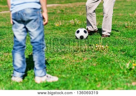 Close up of feet of old man kicking the football ball to his grandchild. The boy and grandfather are standing on grass