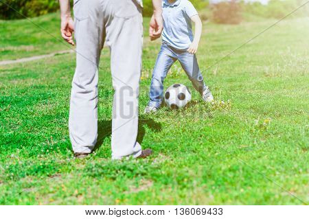 Close up of cheerful grandfather teaching his grandson to play football. The boy is standing near a ball on grass
