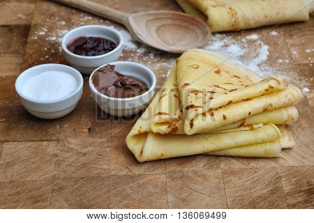 french homemade pancakes with accompaniments on wooden plank