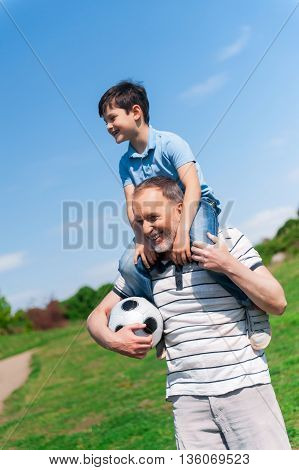 Cheerful old man is playing with his grandson in park. He is holding a boy on his shoulders and the football ball. They are smiling