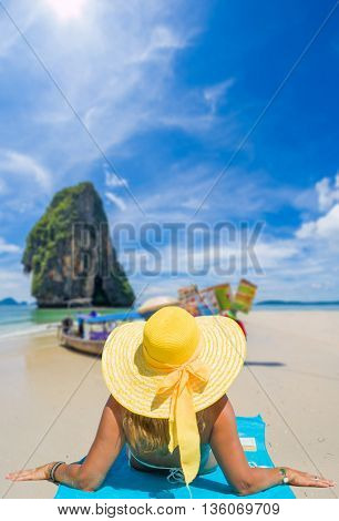 A sexy young woman  wearing a bikini and sun hat sitting on the beach in Krabi Thailand