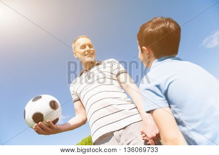 Low angle of cheerful mature man is teaching his grandson to play football. He is holding a ball and smiling. The boy is looking at him with interest
