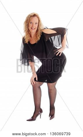 A beautiful blond and happy woman in a black dress standing from front smiling isolated for white background.