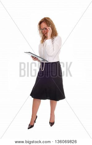 A business woman standing in a black skirt white blouse holding her clipboard looking at isolated for white background.