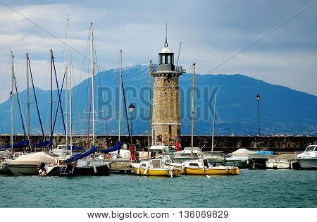 Sirmione Italy - June 1 2006: Stone lighthouse surrounded by moored boats stands on the harbour walls at Lake Garda