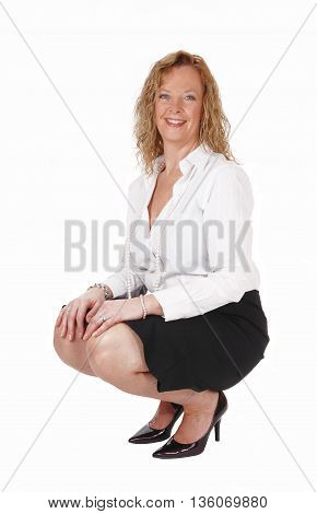 A beautiful blond woman crouching on the floor in a black skirt and white blouse isolated for white background.