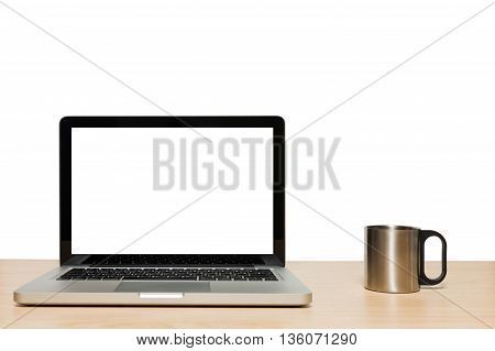 Open laptop with isolated white screen and stainless cup on wooden desk