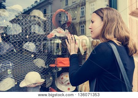 Attractive brunette window shopping. Hand pressed on store window, deciding what to buy.