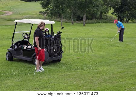 26TH JUNE 2016, BLACKNEST,ENGLAND: A golfer ready to pitch the golf ball onto the green and being watched by another golfer at blacknest golf course in england, 26th june 2016