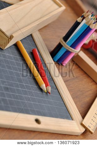 colored pencils on a slate with box and rule on a wooden background