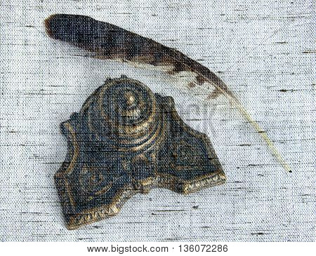 Antique Bronze inkpot with feather on white background with shadows - Photo made with canvas texture effect