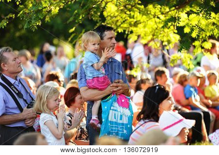 Orel Russia - June 24 2016: Turgenev Fest. Spectators watching play under sunlit trees selective focus